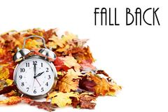 Time Change Daylight Savings with Text. Alarm clock in colorful autumn leaves isolated against a white background with light shadow and shallow depth of field stock image