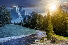 Time change in mountainous summer landscape. Fairy tale mountainous summer landscape at night in full moon light. composite image with high rocky peaks above the Stock Images