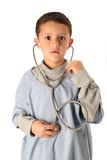 Time for a check up. Young boy listens to his heart in blue scrubs isolated on white Stock Photos