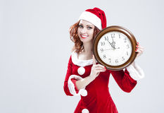 Time and Christmas Holiday Concept. Smiling and Gleeful Red-Haired Santa Helper Showing Time Royalty Free Stock Photo