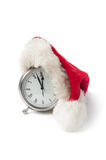 Time for Christmas. Santa hat draped on an alarm clock on a white background stock image