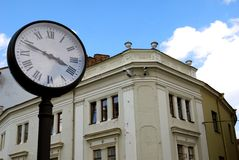 Time and the city. The street clock in front of the ancient building and blue sky Royalty Free Stock Image
