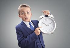 Time on clock shocked and surprised late young executive businessman boy. Concept for appointment, meeting, urgency and running late stock image