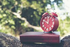 Time clock. time management. red clock and book on wooden nature in the park. Timeline concept 2017 Calendar Wall Background. Timetable planning Royalty Free Stock Photography
