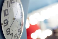 Time. Clock with white dial on blue wall. Side view, little depth of field. Place text on the right. Clock with white dial on blue wall. Side view, little depth Royalty Free Stock Photos