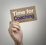 Time for coaching. Hand with brown card is showing Time for coaching with gray background Royalty Free Stock Image