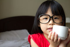 Time for a coffee break. Portrait of a little girl wearing spectacles and hold a cup in hotel room Stock Image