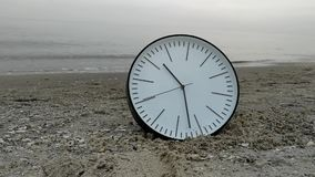 Time Concept Background, White Round Wall Clock in Sand Beach Sea. Time Concept Background, White Round Wall Clock with Black Arrows on Sand Beach of Sea Ocean stock video