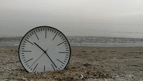 Time Concept Background, White Wall Clock on Sand Beach Foggy Sea Sky. Time Concept Background, White Wall Clock with Black Arrows on Sand Beach of Sea Ocean stock video footage