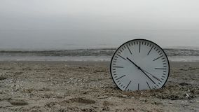 Time Concept Background, White Wall Clock w Black Arrows On Sand Beach Sea Ocean. Time Concept Background, White Wall Clock with Black Arrows on Sand Beach of stock footage