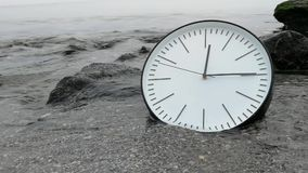 Time Concept Background, White Wall Clock w Black Arrows On Sand Beach Sea Ocean. Time Concept Background, White Wall Clock in the Water, Sea Wave Coming. Idea stock footage