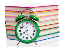 Time concept. Big green alarm clock with pile of books, isolated on white background Stock Images