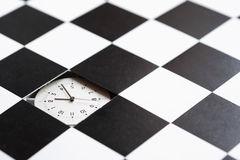 Time Concept. Clock inside hole in black and white checkered surface Royalty Free Stock Photos