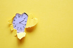Time Concept. Clock inside hole in yellow paper sheet Stock Images