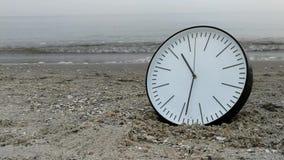 Time Concept, Clock in Sand Beach, Sea Sky Background. Time Concept Background, White Wall Clock with Black Arrows in Sand Beach of Sea Ocean. Idea for Concept stock video