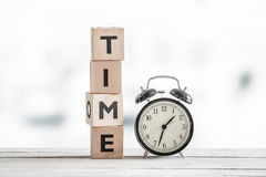 Time concept with a clock and a word. On a wooden table Royalty Free Stock Photography