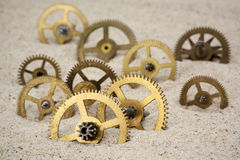 Time concept with a clockwork on the sand Royalty Free Stock Photo