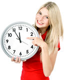 Time concept. five to twelve. Young beautiful woman holding big clock Royalty Free Stock Photography