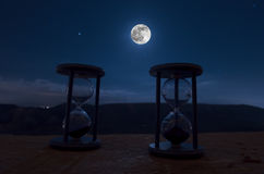 Time concept with a hourglass at night with moon or Sand passing through the glass bulbs of an hourglass measuring the passing tim Stock Image