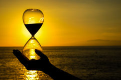 Time Concept. Hourglass and Sun Setting on the Atlantic Ocean Stock Photo