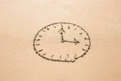 Time concept - Picture of a clock face on sandy beach. Royalty Free Stock Photo