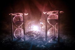 Time concept. Sand passing through the glass bulbs of an hourglass measuring the passing time as it counts down to a deadline. Sil. Houette of Hourglasses in Royalty Free Stock Image