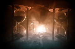 Time concept. Sand passing through the glass bulbs of an hourglass measuring the passing time as it counts down to a deadline. Sil. Houette of Hourglasses in Stock Images
