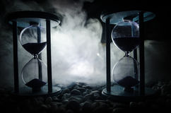 Time concept. Sand passing through the glass bulbs of an hourglass measuring the passing time as it counts down to a deadline. Sil. Houette of Hourglasses in Royalty Free Stock Photo