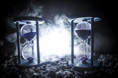 Time concept. Sand passing through the glass bulbs of an hourglass measuring the passing time as it counts down to a deadline. Sil. Houette of Hourglasses in Stock Photo