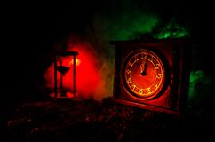 Time concept. Silhouette of Hourglass clock and old vintage wood clock with arrow and smoke on dark background with hot yellow ora Royalty Free Stock Image