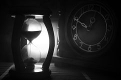 Time concept. Silhouette of Hourglass clock and old vintage wood clock with arrow and smoke on dark background with hot yellow ora Stock Image