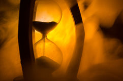 Time concept. Silhouette of Hourglass clock and smoke on dark background with hot yellow orange red blue cold back lighting, or sy Royalty Free Stock Images