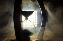 Time concept. Silhouette of Hourglass clock and smoke on dark background with hot yellow orange red blue cold back lighting, or sy Stock Photos