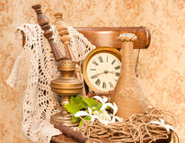 Time concept still life. Antique clock, oil lamp and vase on the oid chair Stock Images