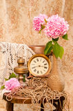 Time concept still life. With antique clock, oil lamp, vintage vase and pink hydrangea Royalty Free Stock Images