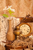 Time concept still life. With antique clock, oil lamp, vintage vase and white hydrangea Royalty Free Stock Image