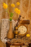 Time concept still life. With yellow flowers, antique clock and oil lamp Stock Photography