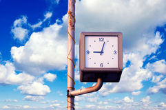 Time concept. Street clock over the blue sky and white clouds Stock Photo