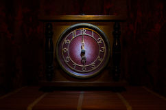Time concept - vintage wood clock face with grunge texture at dark red maroon curtain background, six o clock Royalty Free Stock Image