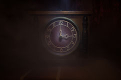 Time concept - vintage wood clock face with grunge texture at dark red maroon curtain background, three o clock with smoke Royalty Free Stock Photography