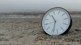 Time Concept, Clock On Sand Beach, Background Walking Man Sea Sky. Time Concept, White Wall Clock w Black Arrows on Sand Beach, Background Walking Man, Sea stock video footage