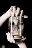 Time concept. Young beautiful girl holding an hourglass in front on a black background Stock Photography