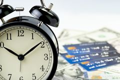 Time countdown or deadline to pay for credit card debt, financial habit concept, alarm clock with many credit cards on US dollar. Banknotes in the background stock image