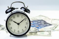Time countdown or deadline to pay for credit card debt, financial problem habit concept, alarm clock with pile of credit cards on. US dollar banknotes in the stock image
