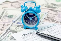 Time or deadline for yearly tax submission concept, miniature small retro alarm clock with pen on 1040 US individual income tax. Filling form on pile of US royalty free stock photo