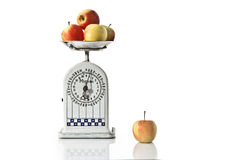 Time for diet. An old scale with fresh apples on white background Royalty Free Stock Photo
