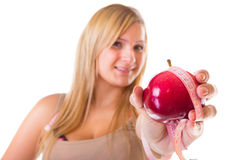 Time for diet slimming. Woman with apple and measuring tape Stock Photography