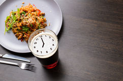 Time for dinner with beer. Clock silhouette on foam in beer glass on black table with food, view from above Stock Photos