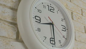 Time eight hours thirty minutes. Timelapse. Round white clock hanging on brick wall. stock video