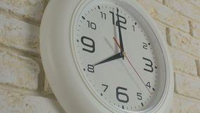 Time eight hours. Timelapse. Round white clock hanging on brick wall. stock footage